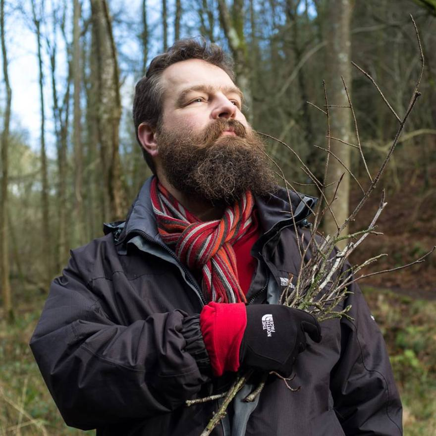 Oliver Cameron-Swan standing heroically in a wood holding a handful of twigs over his heart. He has an impressive beard that his loving family refuse to let him shave off, although his beautiful wife does trim it for him from time to time. It must have been cold when this picture was taken because he is wearing a coat, gloves, and a scarf, though no hat, he doesn't do hats very often #nohat.